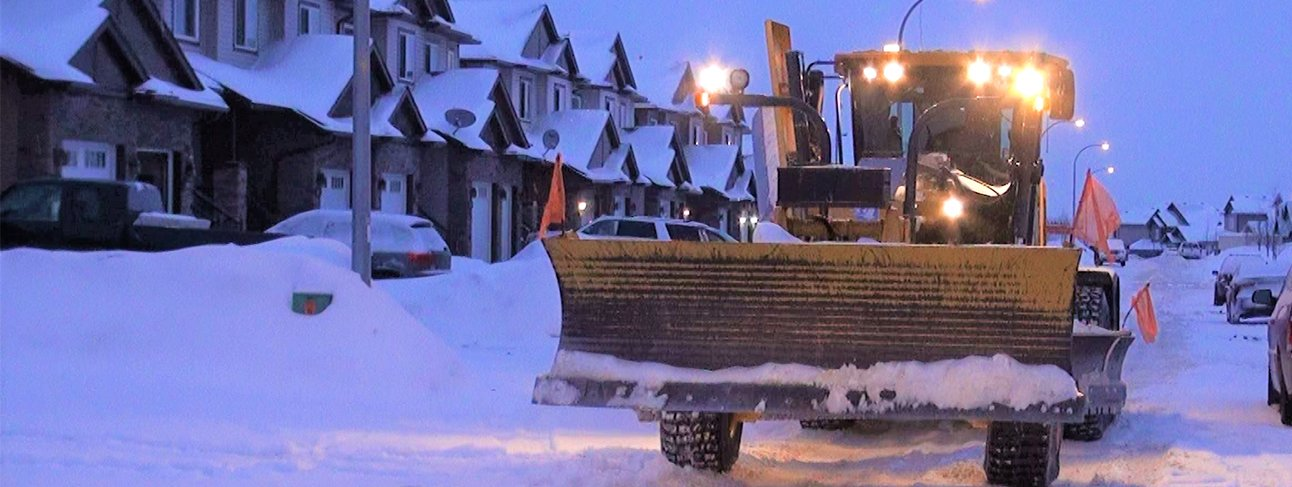 Snow removal grader on residential street