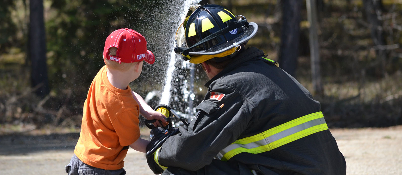 Child with firefighter spraying water