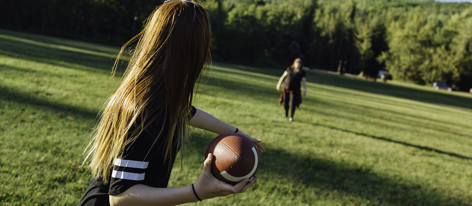 Girl throwing a football in a park